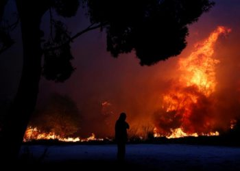 A man looks at the flames as a wildfire burns in the town of Rafina, near Athens. REUTERS/Costas Baltas