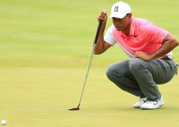 Tiger Woods inspects the lay of the green before taking his shot Friday