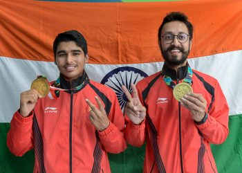 Gold medal winner Saurav Chaudhary (L) and bronze medallist Abhishek Verma pose for photographs during the medal presentation ceremony of men's 10m air pistol event at the Asian Games in Palembang