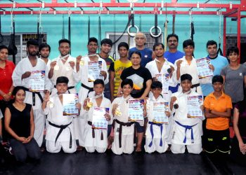 Karatekas pose with their medals and certificates at Utkal Karate School in Bhubaneswar, Tuesday