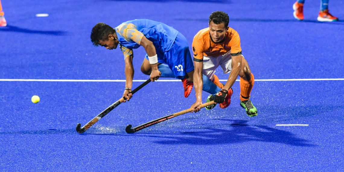 India's Vivek Prasad (L) tries to hit the ball during their men's hockey semifinal match against Malaysia at the Asian Games