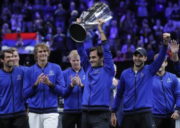 Team Europe's Roger Federer hoists the winners' trophy as he celebrates with teammates after defeating Team World in the Laver Cup tennis tournament in Chicago, Sunday