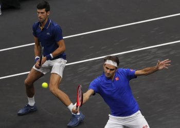 Team Europe's Roger Federer (R) and Novak Djokovic play against Team World's Jack Sock and Kevin Anderson during a men's doubles tennis match at the Laver Cup, Friday