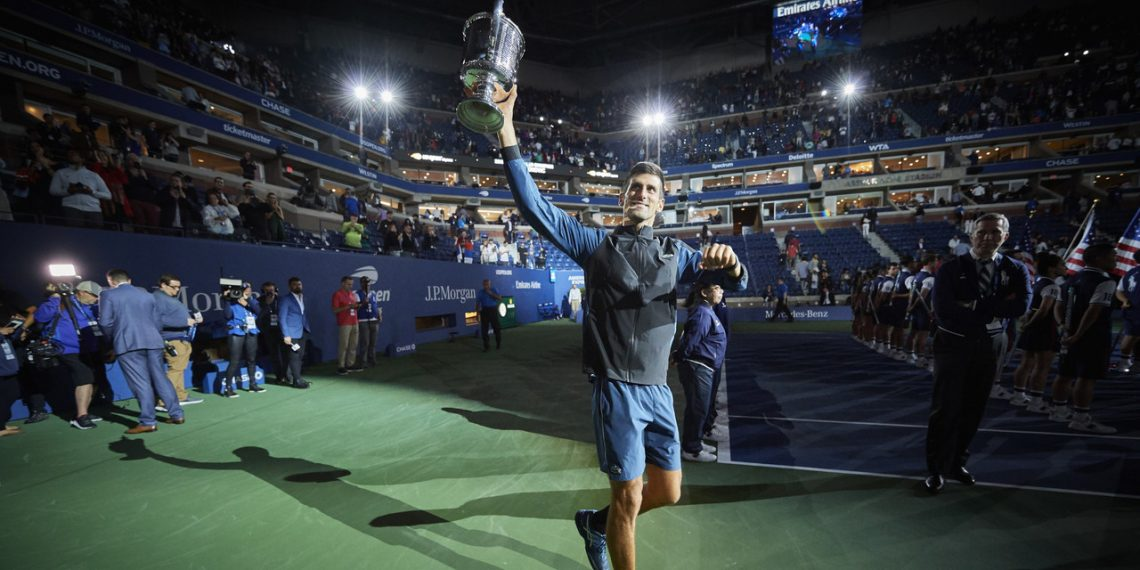 Novak Djokovic celebrates with the US Open winner's trophy