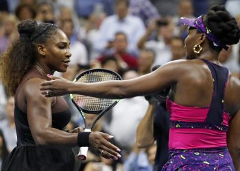 Serena Williams (L) meets her sister Venus after their match during the third round of the US Open tennis tournament, Friday