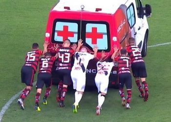 Players of both Flamengo and Vasco trying to push the ambulance which had broken down on the pitch while carrying an injured footballer