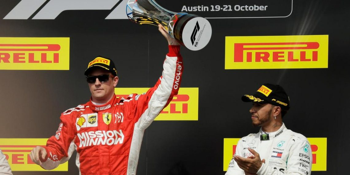 Kimi Raikkonen (L) holds the winner's trophy aloft in celebration as Lewis Hamilton applauds the Finn at Austin, Sunday