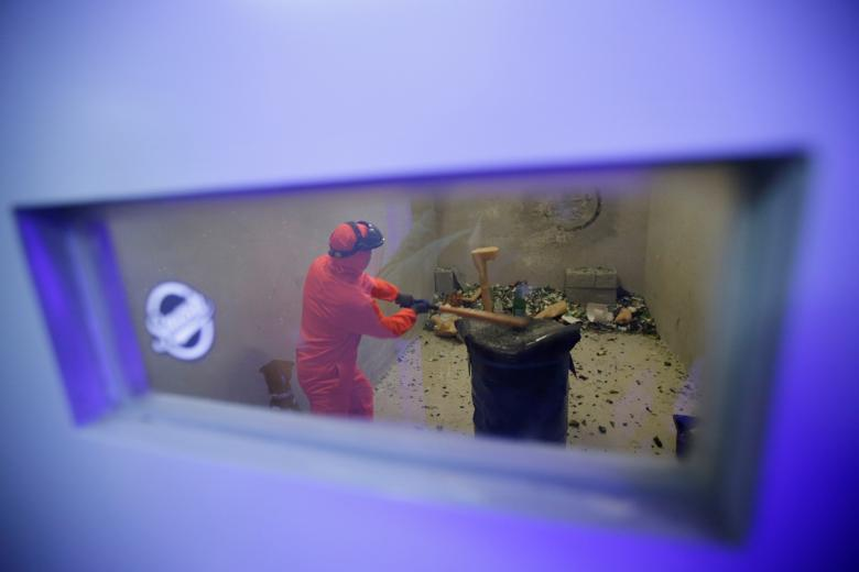 Customer Liu Chao, wearing protective gear, is seen through a window as he smashes bottles in an anger room in Beijing, China. REUTERS/Jason Lee