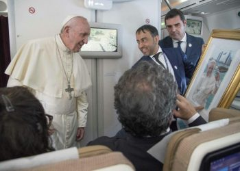 "Pope Francis, shown here accepting a gift from an Arab journalist aboard the papal plane, said the problem of sexual abuse by priests could be found ""anywhere"" (AFP)"