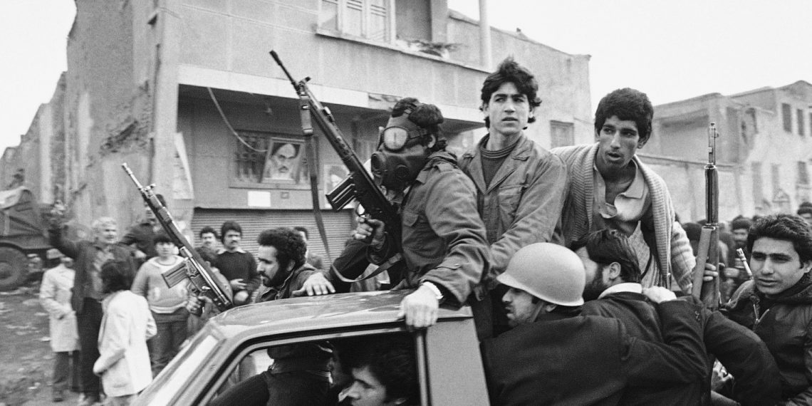 FILE - In this Feb. 12, 1979 file photo, armed rebels, one wearing a gas mask, ride in a truck near the headquarters of Ayatollah Khomeini in Tehran, Iran. Forty years ago, Iran's ruling shah left his nation for the last time and an Islamic Revolution overthrew the vestiges of his caretaker government. The effects of the 1979 revolution, including the takeover of the U.S. Embassy in Tehran and ensuing hostage crisis, reverberate through decades of tense relations between Iran and America. (AP)