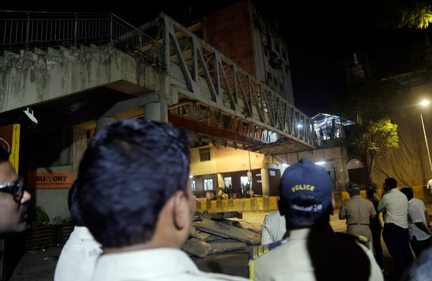 Policemen and others gather near a pedestrian bridge that collapsed in Mumbai. (AP)