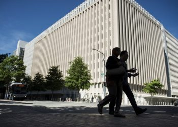 People walk past the World Bank Group's headquarters May 3, 2013 in Washington, DC. (BRENDAN SMIALOWSKI/AFP/Getty Images)